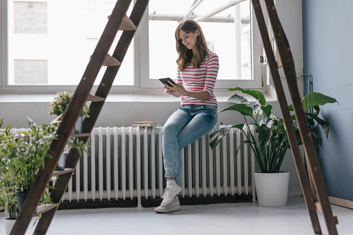 Woman sitting on radiator in her new home, reading e-book, surrounded by plants - gettyimageskorea