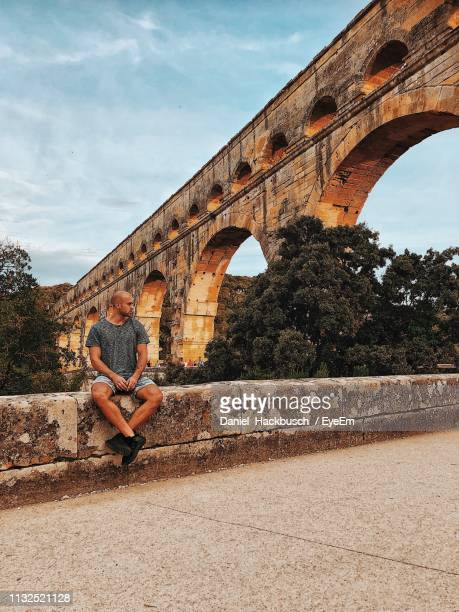 woman sitting on railing against arch bridge - gard stock photos and pictures