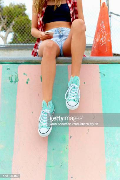 Woman sitting on ramp at skate park