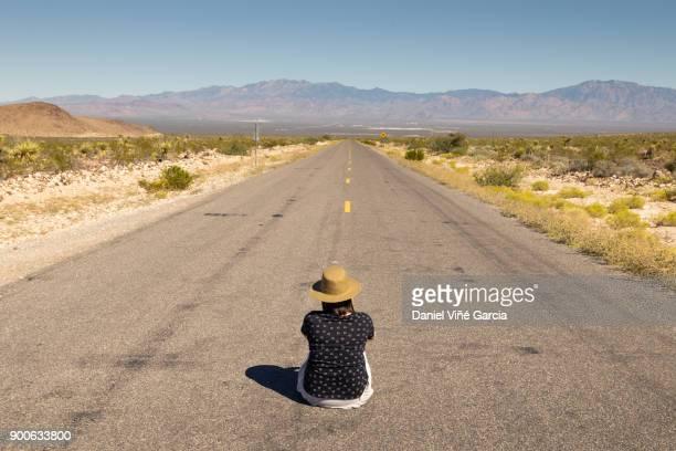 Woman sitting on remote desert road