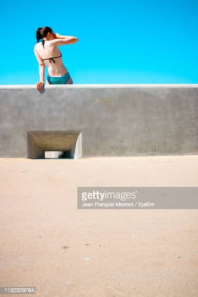 Woman Sitting On Retaining Wall At Beach Against Clear Sky