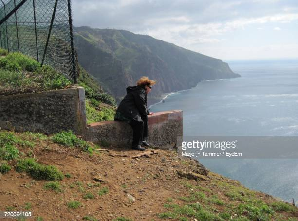 Woman Sitting On Retaining Wall While Looking At Sea From Ponta Do Pargo