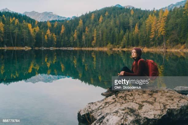 女岩の上に座って、アイプゼー湖のアルプスの美しい景色を見て