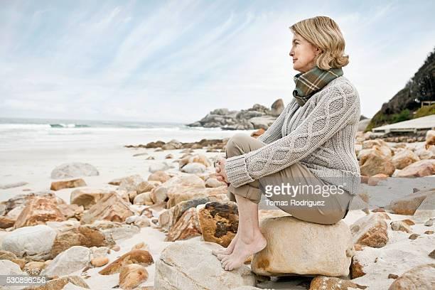 woman sitting on rock at the beach - einzelne frau über 30 stock-fotos und bilder