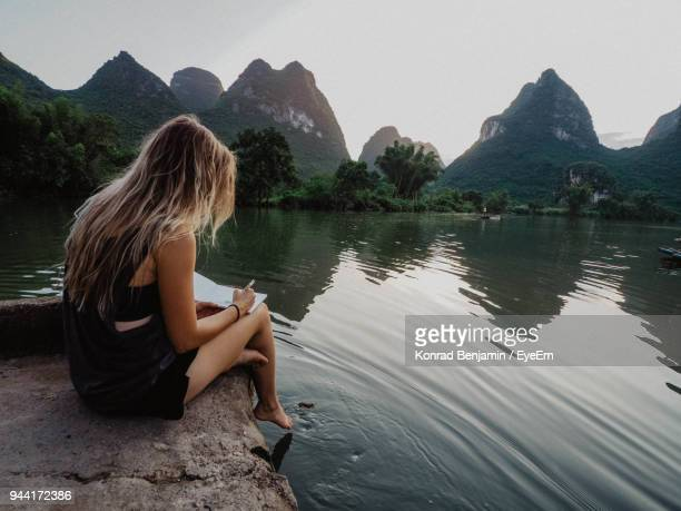 Woman Sitting On Rock By Lake Against Clear Sky