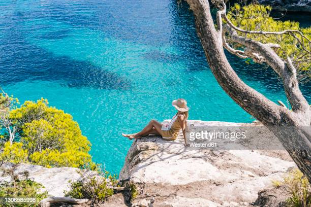 woman sitting on rock by sea during sunny day - balearic islands stock pictures, royalty-free photos & images