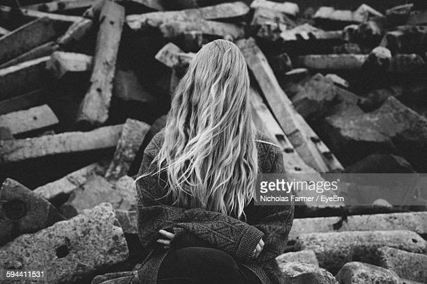 Woman Sitting On Rock Covering Face With Hair