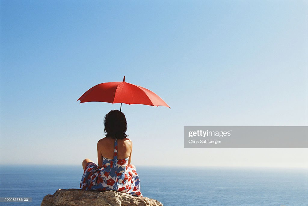 woman sitting on rock facing sea holding umbrella rear view stock