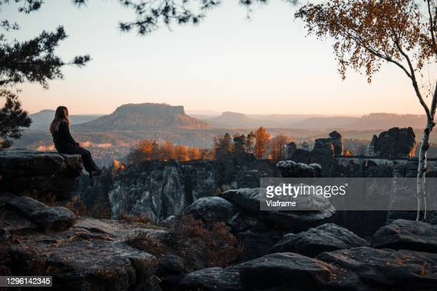 woman sitting on rock formation watching the sunset - saxony stock pictures, royalty-free photos & images