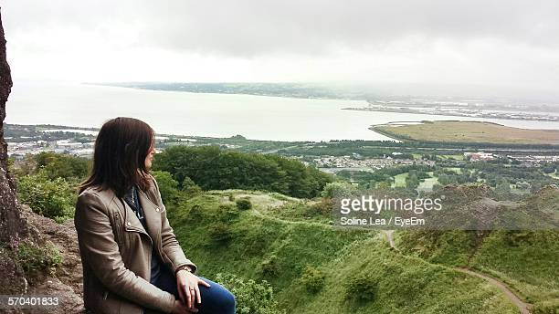 Woman Sitting On Rock Looking At Scenic View Of Sea