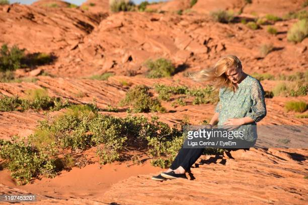 woman sitting on rock - liga cerina stock pictures, royalty-free photos & images