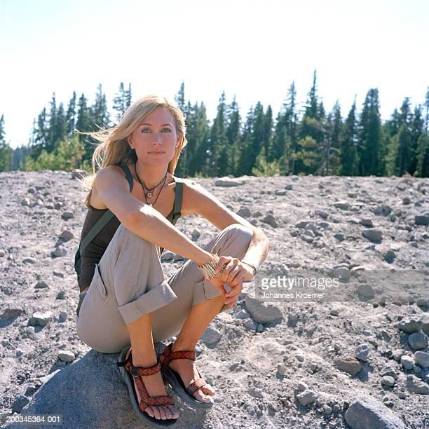 Woman sitting on rock, portrait