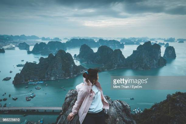 woman sitting on rock while looking at sea against sky - pretty vietnamese women stock pictures, royalty-free photos & images