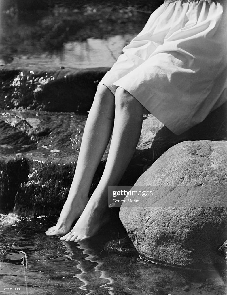 Woman sitting on rock with feet in water, low section : Stock Photo