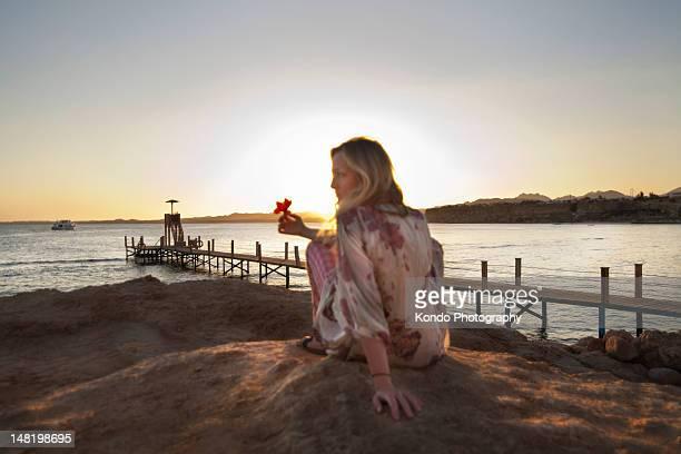 Frau sitzt auf felsigen Strand