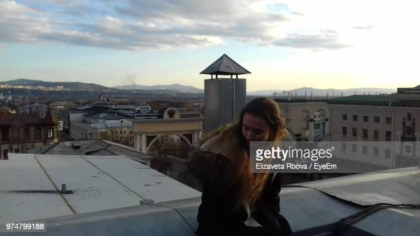 woman sitting on roof in city during sunset - teen russia stock photos and pictures