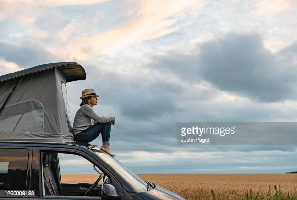 woman sitting on roof of camper at sunset - escaping stock pictures, royalty-free photos & images
