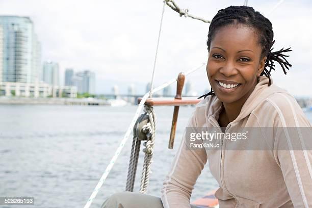 Femme souriante, assis sur le bateau à voile