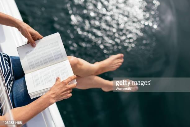 woman sitting on sailing boat, reading a book - ocio fotografías e imágenes de stock