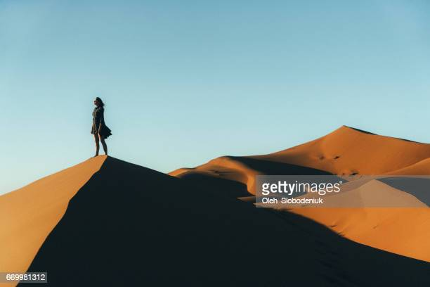 Woman sitting on sand  in the desert