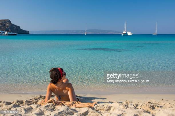 woman sitting on shore against sea at beach - peloponnese stock photos and pictures