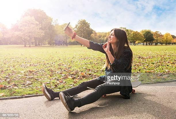 Woman sitting on skateboard taking a selfie