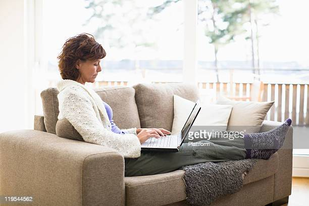 Woman sitting on sofa and surfing internet