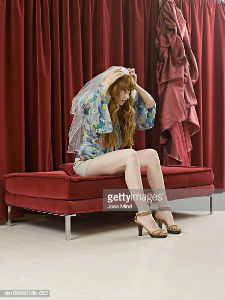 Woman sitting on sofa and trying on bridal veil