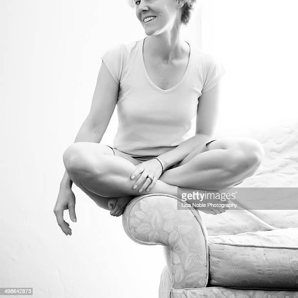 Woman Sitting on Sofa Arm