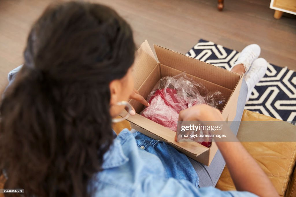 Woman Sitting On Sofa At Home Opening Online Clothing Purchase : Stock Photo