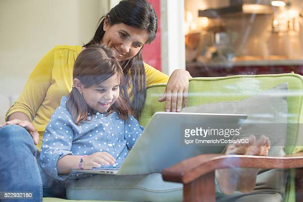 Woman sitting on sofa by daughter (8-9) using laptop in room behind glass wall, Barcelona, Spain