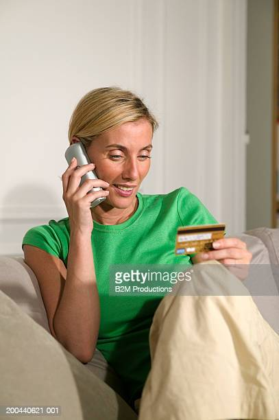 Woman sitting on sofa holding bank card while using mobile phone
