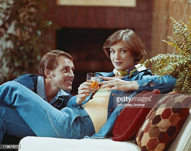 woman sitting on sofa holding drink - 1976 stock pictures, royalty-free photos & images
