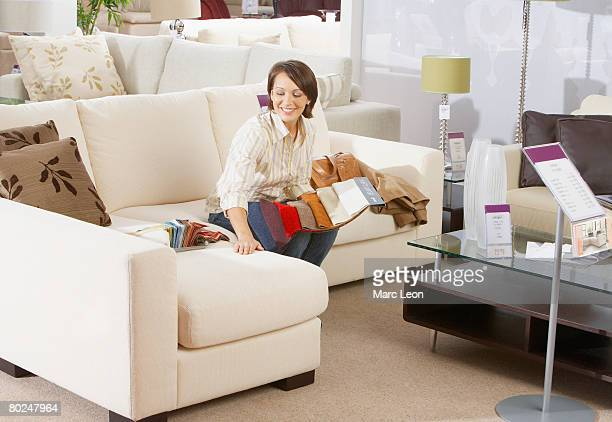 Woman sitting on sofa in furniture store.