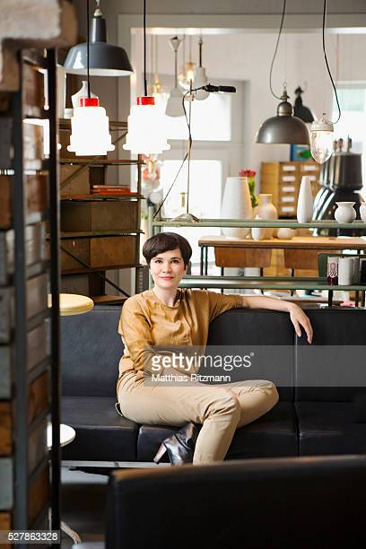 Woman sitting on sofa in her studio