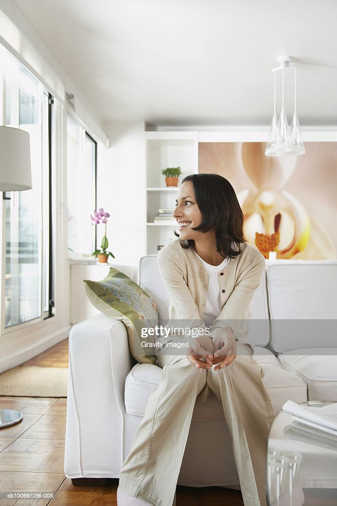 Woman sitting on sofa in living room, looking away, smiling : Stockfoto