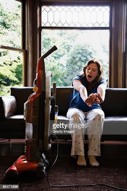 woman sitting on sofa, looking at vacuum - haushaltsaufgabe stock-fotos und bilder