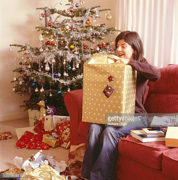 Woman sitting on sofa opening Christmas presents, smiling