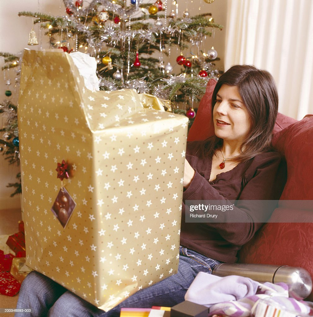 woman sitting on sofa opening christmas presents smiling stock photo