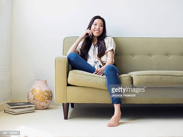 woman sitting on sofa - divano foto e immagini stock