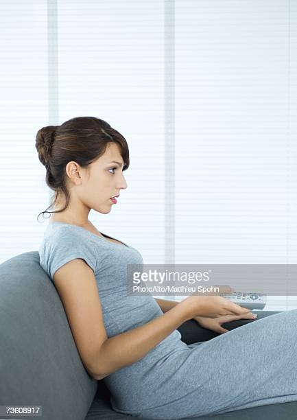 Woman sitting on sofa, pointing remote control, side view