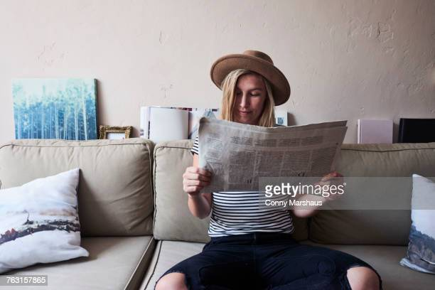Woman sitting on sofa, reading newspaper
