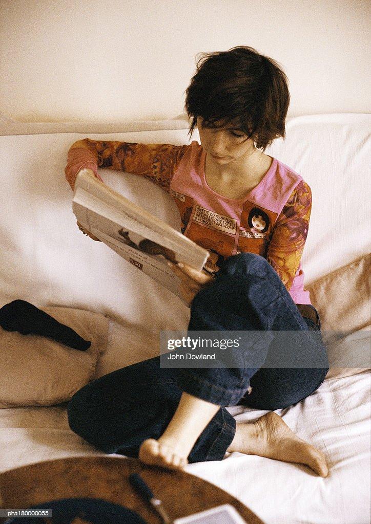 Woman sitting on sofa, reading : Stockfoto