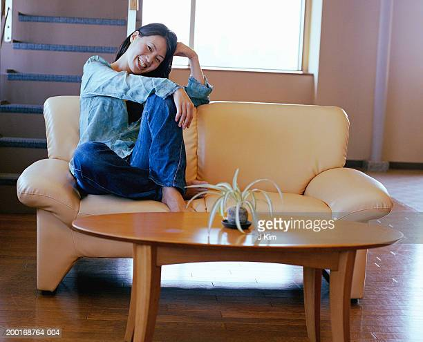 Woman sitting on sofa, resting head on hand, smiling, portrait