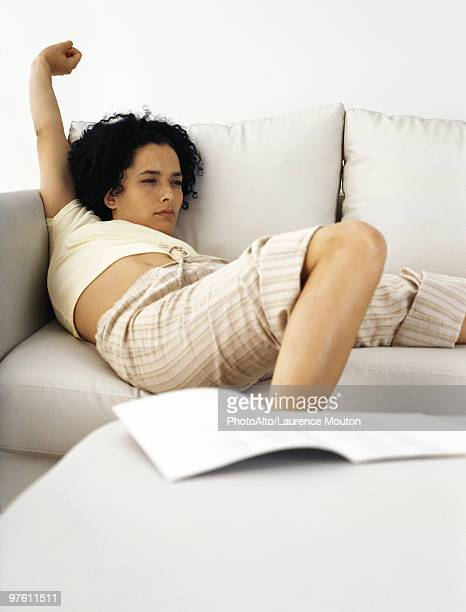woman sitting on sofa stretching - bad posture stock pictures, royalty-free photos & images
