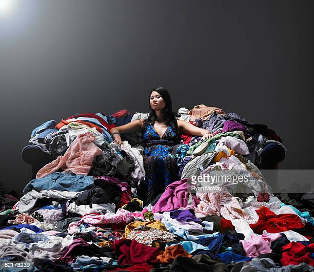 woman sitting on sofa surrounded by clothes. - heap stock pictures, royalty-free photos & images