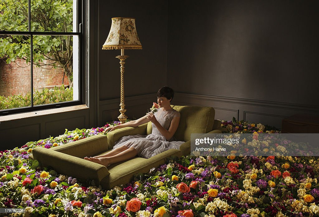 Woman sitting on sofa surrounded by flowers : Stock Photo