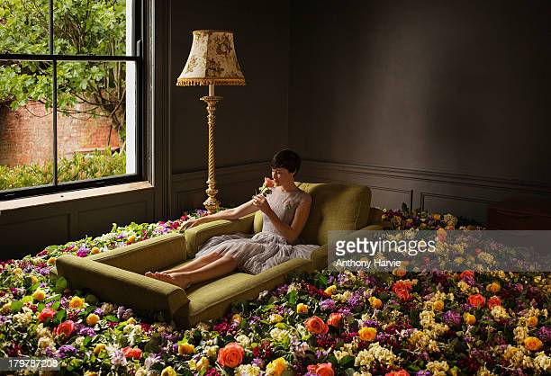 woman sitting on sofa surrounded by flowers - vestido de colores fotografías e imágenes de stock