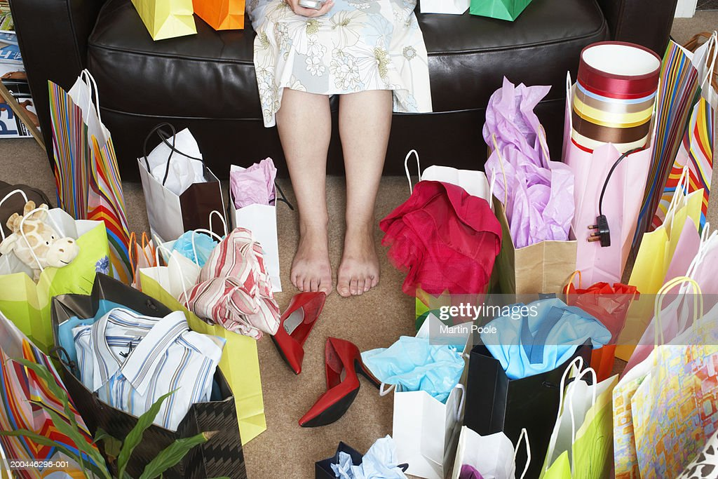 Woman sitting on sofa surrounded with shopping bags : Stock-Foto