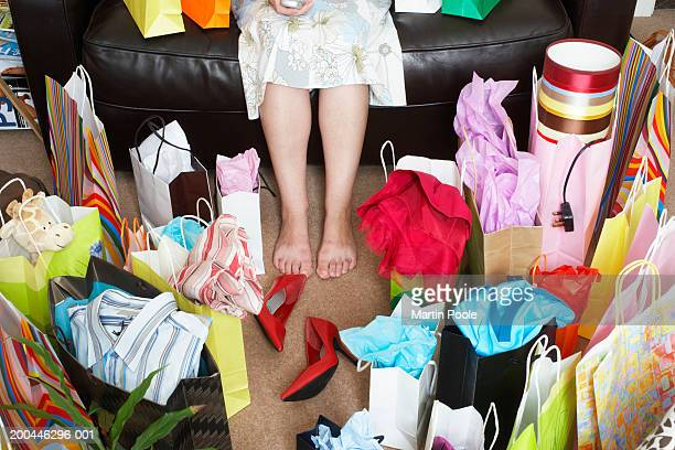 woman sitting on sofa surrounded with shopping bags - excesso imagens e fotografias de stock